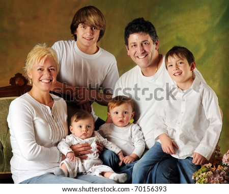 A family portrait composed of Mom, Dad and four sons -- a baby, preschooler, elementary boy and young teen.