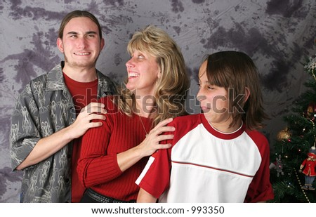 A family posing for a Christmas portrait.  The older son has just passed gas and the mother and younger son are reacting.