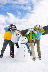 A family posing next to a snowman on a ski slope while pretending to cover their eyes with snowballs for fun