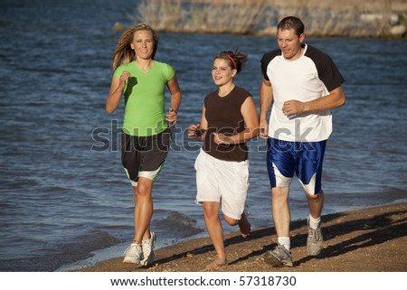 A family running and spending time together at the beach exercising and enjoying each other.