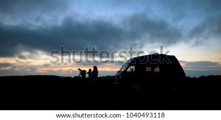 A family searching the night sky for stars looking through a telescope. They travelled in a VW campervan which sits behind them. A beautiful colourful sky creates a lovely background.