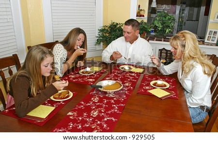 A family sitting around the dinner table enjoying pumpkin pie.