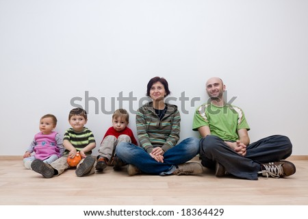 A family sitting in an unfurnished room of their new house.