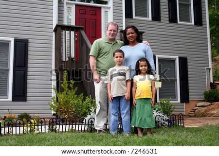 A family standing in front of their home