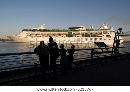 a family watches from the dock as a cruise ship leaves the Port of New Orleans, headed down the Mississippi River toward Mexico