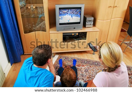 a family watching tv with tv