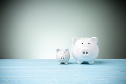 A family white piggy banks on blue wooden  and behind green background with copy space. Concept savings, investment, save money in the future.