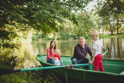 A family with a daughter and son swim in a park on a boat on the river. Dad helps, teaches his son to paddle. In the background mom with a small daughter. Family summer vacation concept