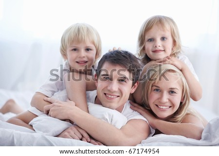 A family with two children on a bed in the bedroom