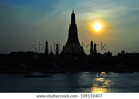 A famous temple of Thailand, Wat Po, in silhouette by the river