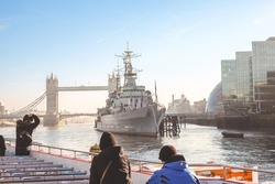 A famous warship in London as known as HMS Belfast with tourists in foreground and a famous attractive place as known as Tower Bridge and towers behind in the background.