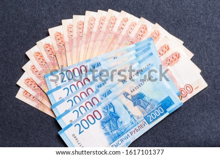 A fan of five thousandth and two thousandths notes of Russian rubles on a dark background. The concept of ruble instability, inflation, economic decline.