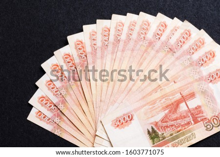 A fan of five thousandth notes of Russian rubles on a dark background. The concept of ruble instability, inflation, economic decline.