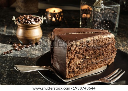 A fancy piece of chocolate cake (Sacher Torte) on a cake slice, a copper jar of coffee beans and a illuminated candel holder are in the out of focus area in the backtrop Zdjęcia stock ©