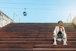 A fancy young African female is sitting on the wooden steps of the stair and using her smartphone to choose the best tourist route, a ropeway car in the background, a copy space place on the left