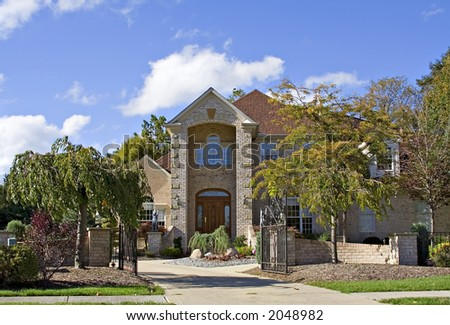 A fantastic beautiful American home surrounded my a well-manicured and landscaped yard in early autumn. - stock photo