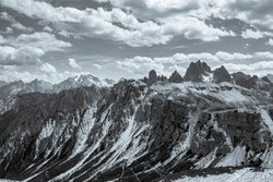 A fantastic black and white image of rocky mountains and cloudy skies in the Italian Dolomites, Northern Italy.