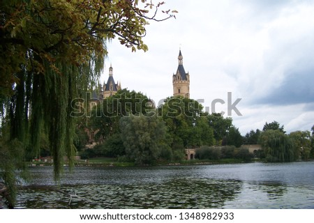 A fantastic view of a Schwerin Castle a lake, water lilies, a bank, some pebbles and a lot of trees #1348982933