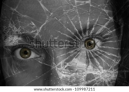 A fantastical photo of a green eyed woman peering through the shards of a broken pane of glass