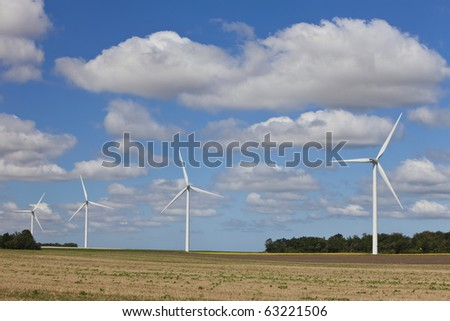A farm of four wind turbines or windmills providing alternative sustainable green energy.