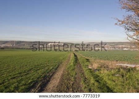 A Farm track dissappears into the valley across a Green Field under a blue sky