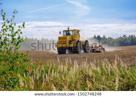 A farm tractor cultivates land after harvesting grain.  #1502748248