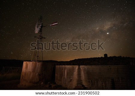 Stock Photo A farm wind pump is seen against the milky way solar system in this night photograph