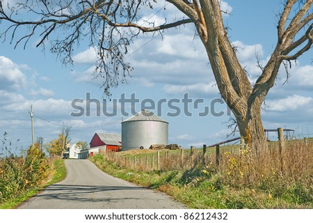 A farm with a red barn and a huge silo sits along a country road in Kentucky.