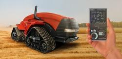A farmer controls an autonomous tractor through a smartphone mobile application