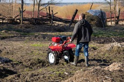 A farmer man plows the land with a cultivator. machinery cultivator for soil cultivation in the garden, motor cultivator.