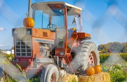A farmer's tractor displays an autumn bounty in countryside. A tractor decorated with hay and pumpkins for Thanksgiving Day and Halloween Festival. Street photo, selective focus, travel photo, nobody