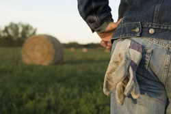 A farmer stands in a field in front of a hay bail