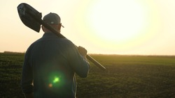 A farmer with a shovel in his hands walks across the field with a shovel in the sun. An agronomist walks on a black fertile plowed land at sunset. Worker with a shovel in a field at sunset.