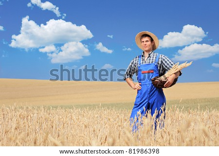 A farmer with panama hat posing in a wheat field