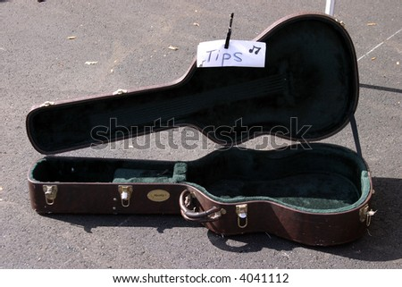 a farmers market series a guitar case with a tips for playing music sign