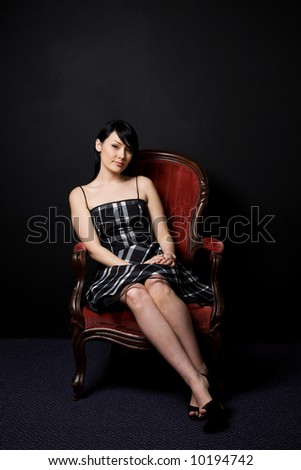 A fashion shoot of a beautiful woman sitting on a vintage chair