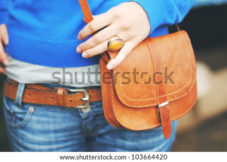 A fashion shoot of a woman in blue jeans and a blue sweater, wearing a ginger ring, a ginger leather belt and holding a ginger leather bag in her hand