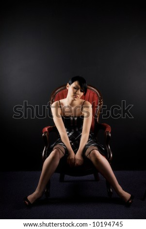 A fashion shot of a beautiful sad woman sitting on a vintage chair