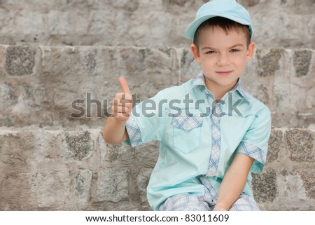 A fashion smiling boy is sitting on the stone steps