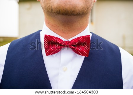 A fashionable groom wears a red and white bowtie with a navy blue vest on his wedding day.