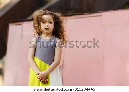 a Fashionable little girl with brown hair posing on wall background pink