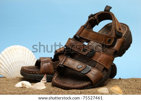 A fashionable shot of a pair of males leather sandals on a beach scene.
