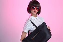A fashionable young girl wearing sunglasses, showing off a black purse