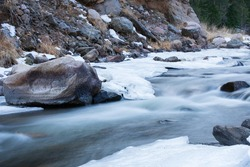 A fast moving stream with rocks and rapids on the Front Range of Colorado. The Big Thompson River flowing with ice along the edges.  Boulders and fast moving river.