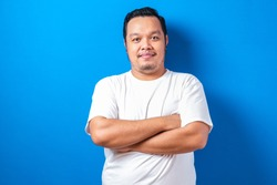 A fat asian man wearing a white t-shirt standing with his arms crossed while smiling at the camera. The man shows confident gesture, against blue background.