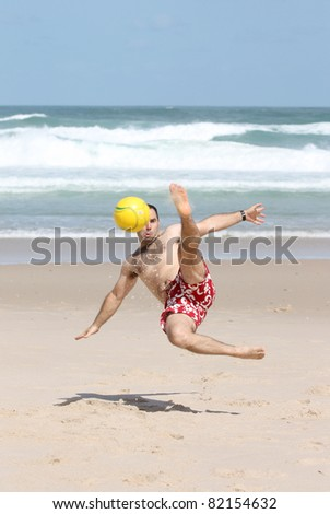 A fat man playing with a ball on the beach