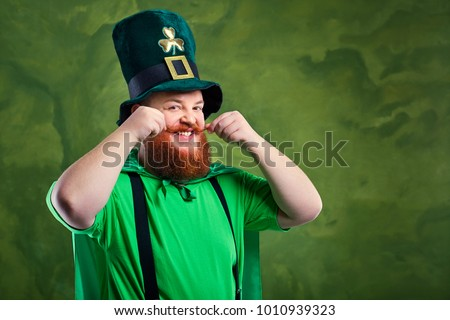 A fat man with a beard in St. Patrick's suit is smiling.