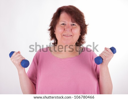 A fat woman is doing exercises with barbells
