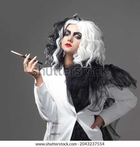 A fatal beauty in a daring fashion image with black and white hair. A rebellious stylish image for Halloween. a young woman in a black and white outfit smokes a cigarette using a mouthpiece ストックフォト ©