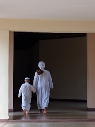 A father and his son enter a mosque